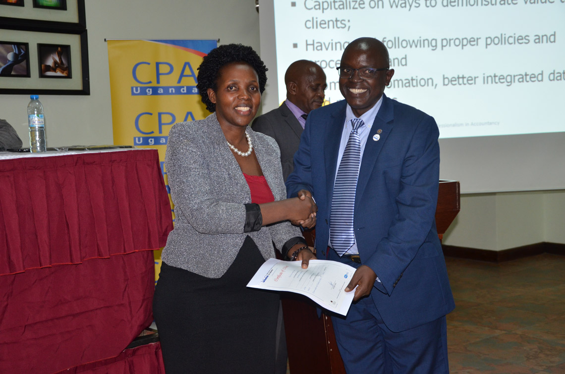 CPA Kelemensio Busingye (L) received a certificiate in honour of her presentation. CPA Constante Mayende (R) handed the certificate